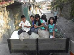 Niños juegan entre los costales de trigo